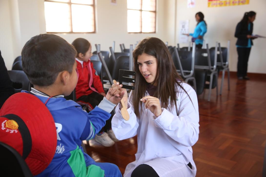 Projects Abroad volunteer explains an eye test to a local boy during her spring break in Peru.